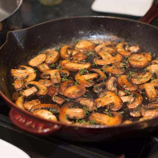 mushrooms browning in a cast iron pan. sprinkles with fresh thyme.