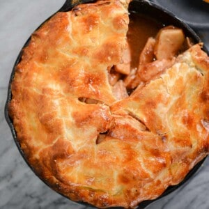 apple pie baked in a cast iron pan with a slice cut out