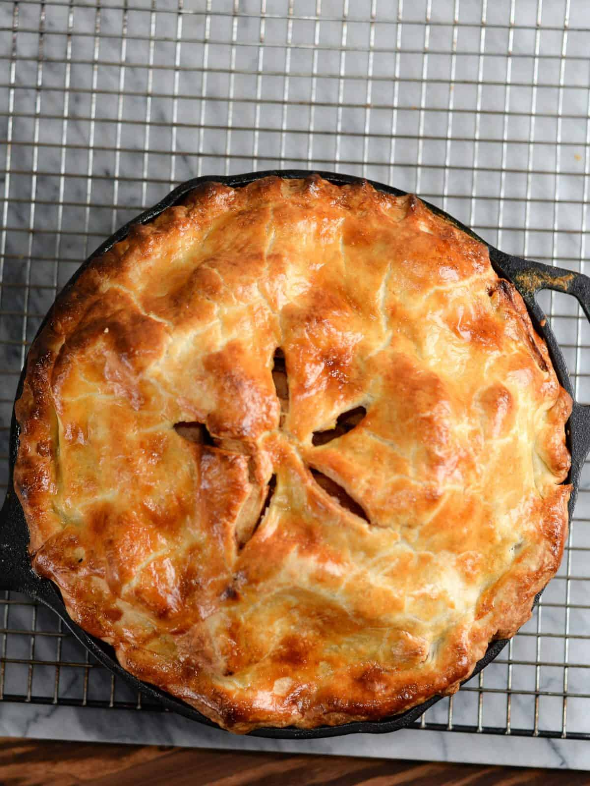apple pie baked in a cast iron skillet cooling on a wire baking rack.