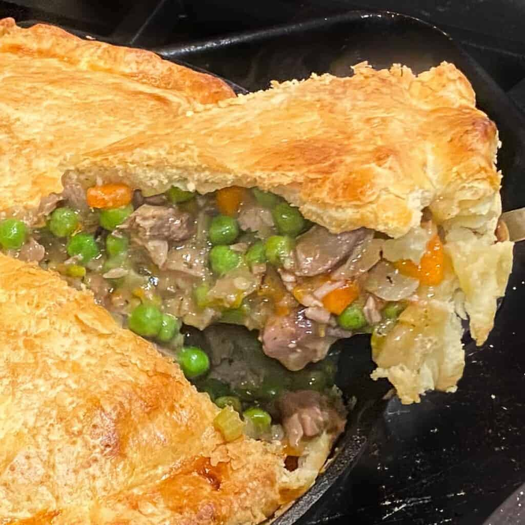 easy turkey pot pie baked in cast iron, a slice being cut out