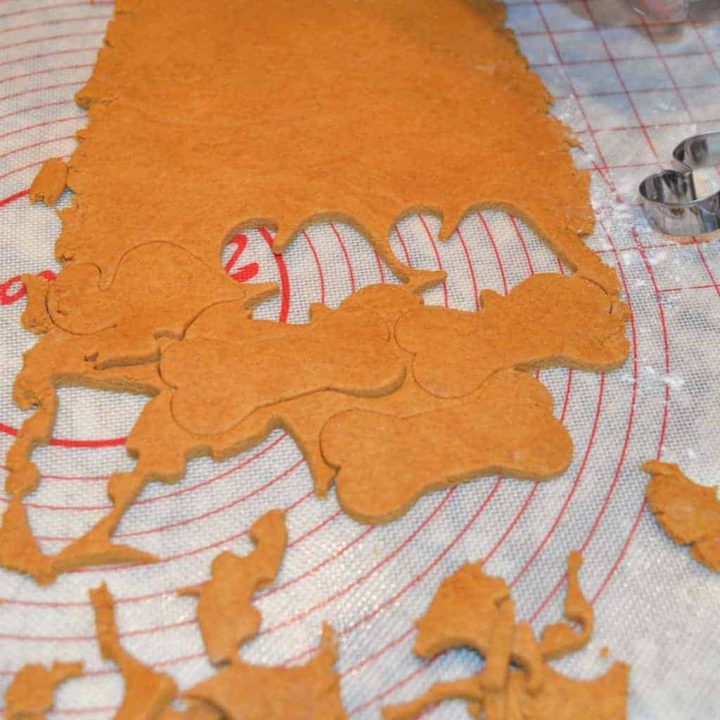 peanut butter dough for dog treats rolled out with cookie cut out of it.   foodology geek