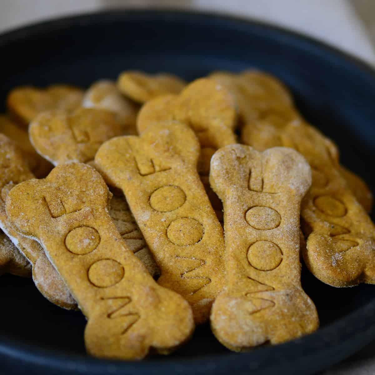 homemade peanut butter dog treats shaped like bones on a black plate | foodology geek