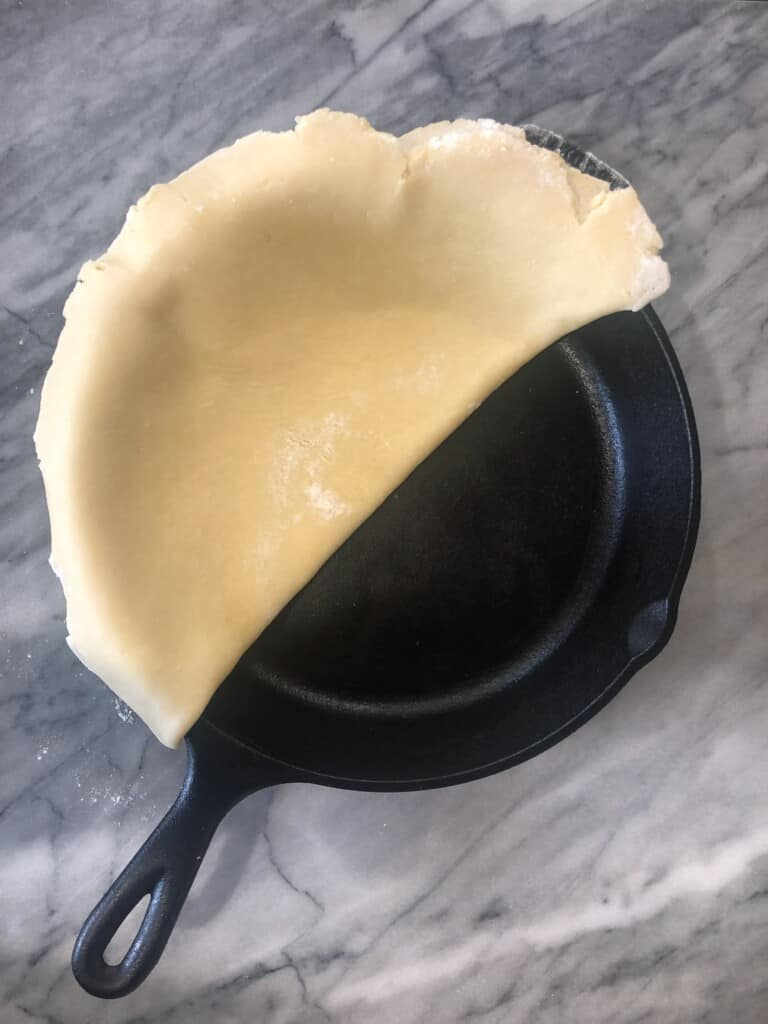 pie crust folded in half and added in to a cast iron pan