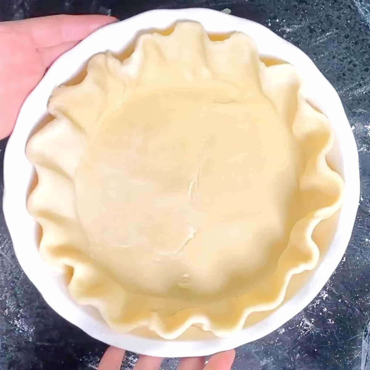 easy all butter pie dough recipe in a white pie dish.