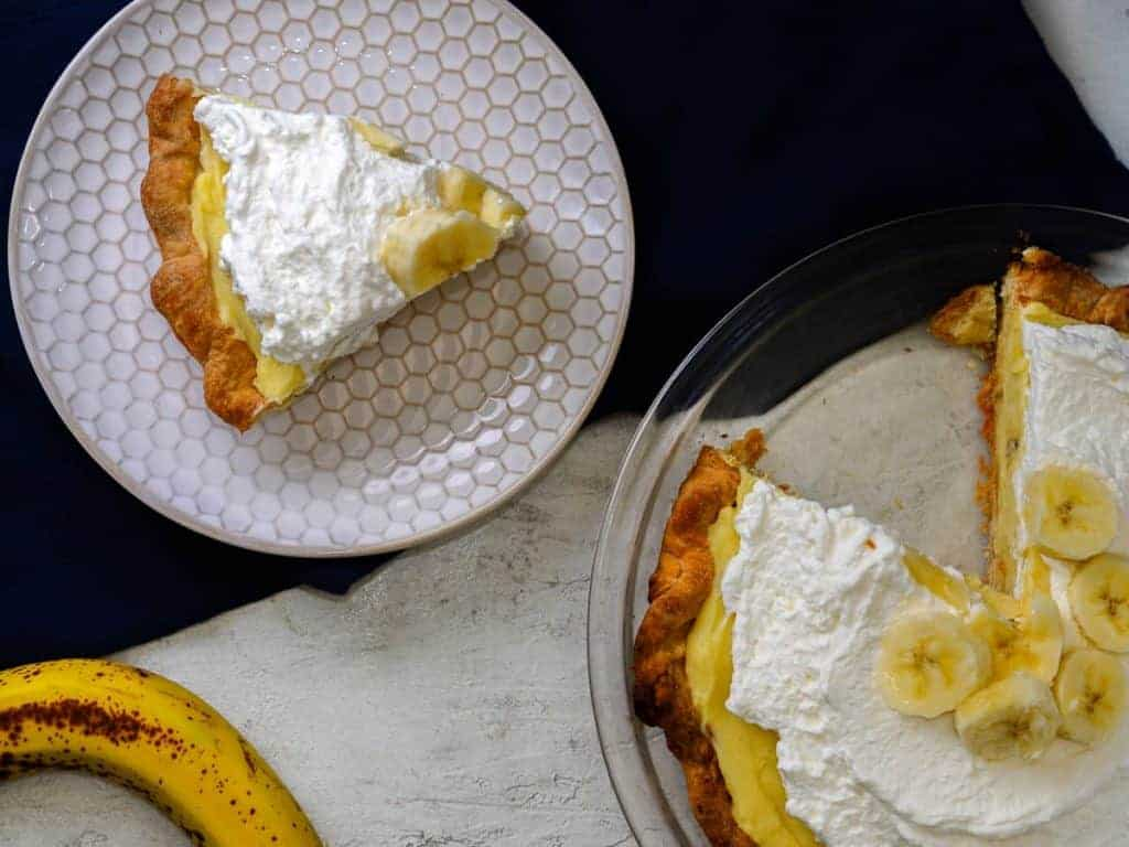 Slice of banana cream pie next to the full banana cream pie.