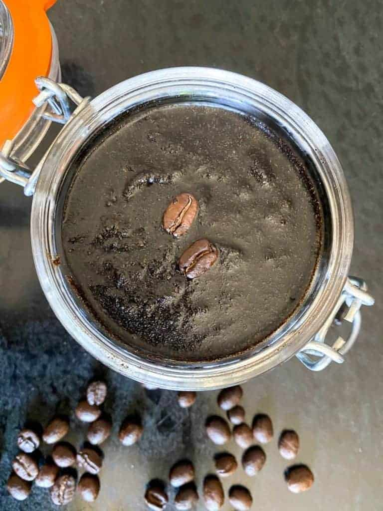 facial coffee scrub in a jar surrounded by loose coffee beans. recipe by foodology geek.