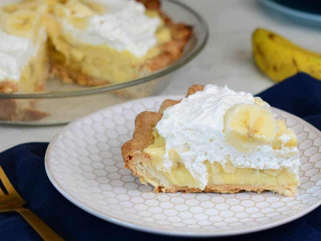 slice of banana cream pie topped with whipped cream and fresh bananas.