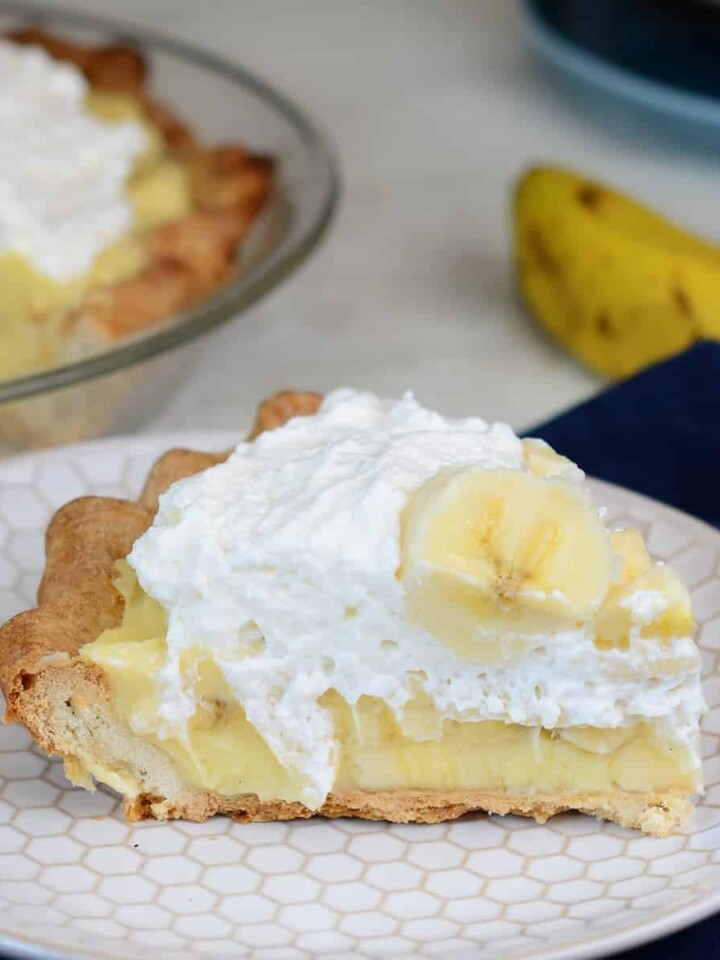 slice of fresh banana cream pie. topped with whipped cream and more fresh bananas.