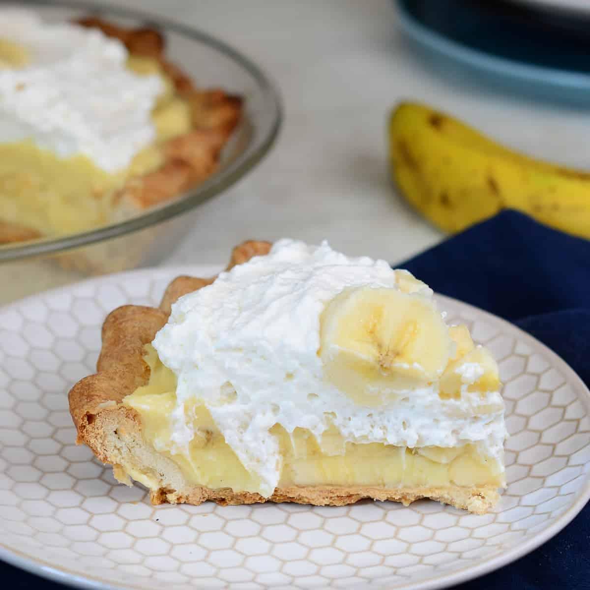 slice of fresh banana cream pie. topped with whipped cream and more fresh bananas.