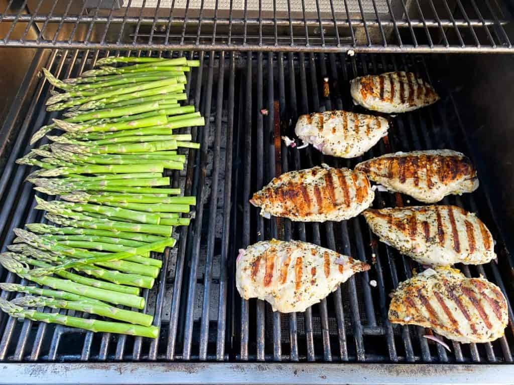 grilled chicken breasts and asparagus on a grill