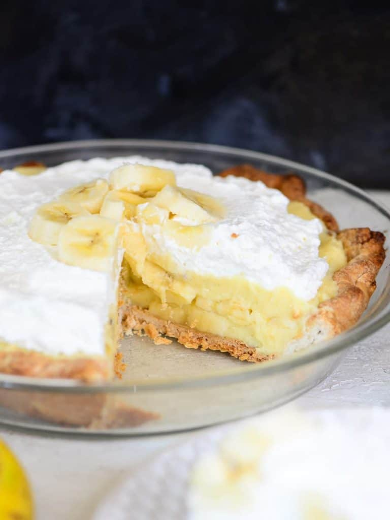 layers of vanilla custard and fresh bananas, one slice missing from a banana cream pie.