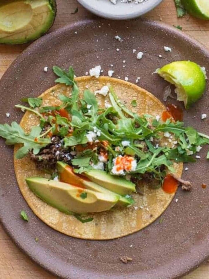 easy shredded beef tacos served with corn tortillas, avocado, cotija, and tapatio