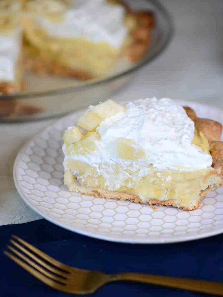 slice of banana cream pie topped with whipped cream and fresh bananas | foodology geek