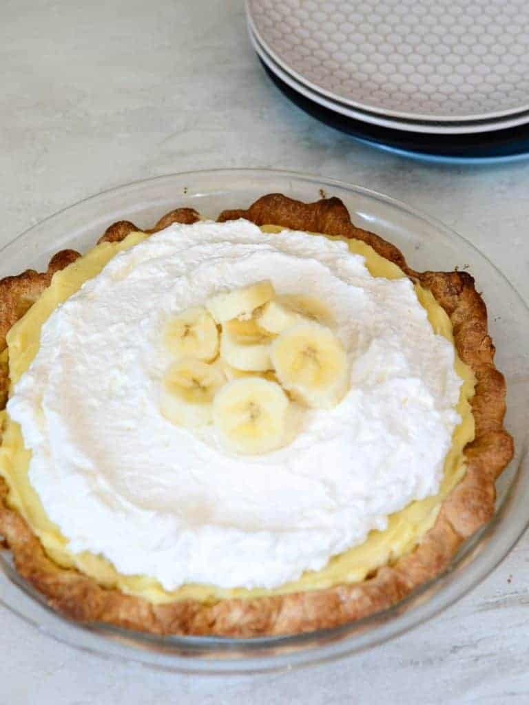 top the banana pie with fresh whipped cream and more fresh bananas