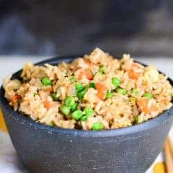 vegetable fried rice with egg in a black bowl