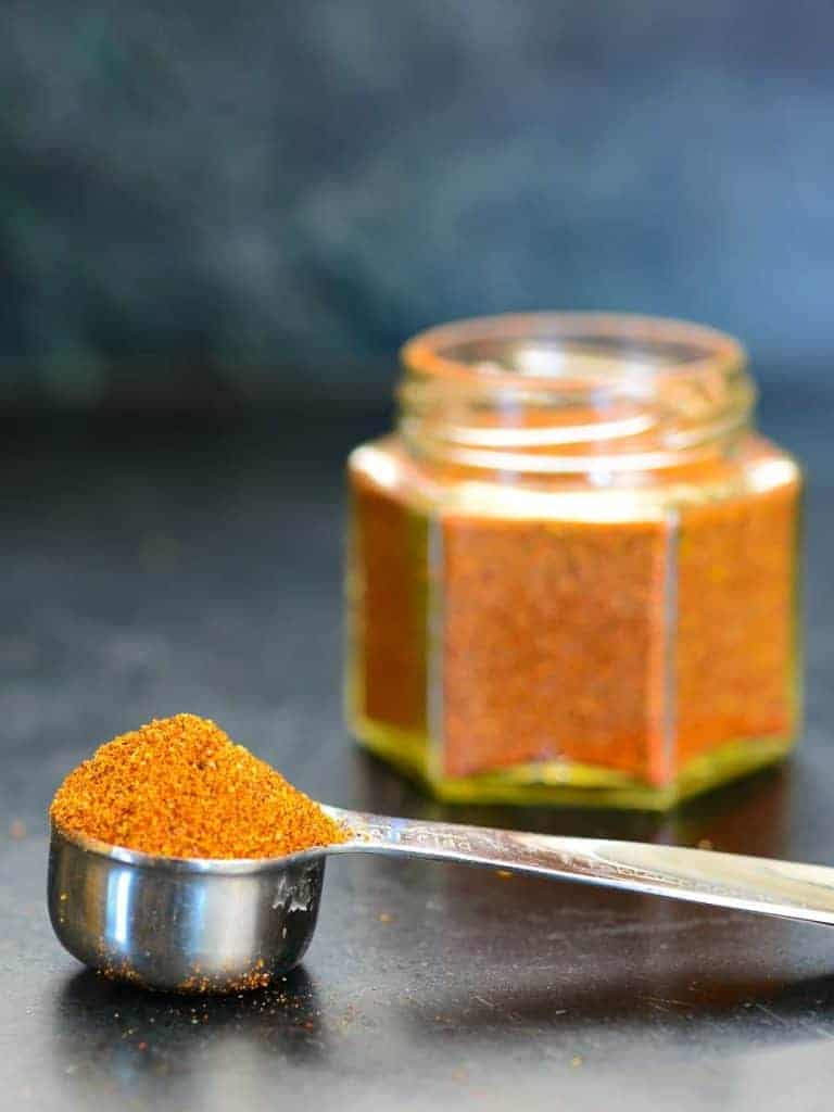 scoopful of bbq rub with the jar in the background | foodology geek