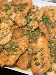 a platter of easy chicken piccata with lemon sauce and capers