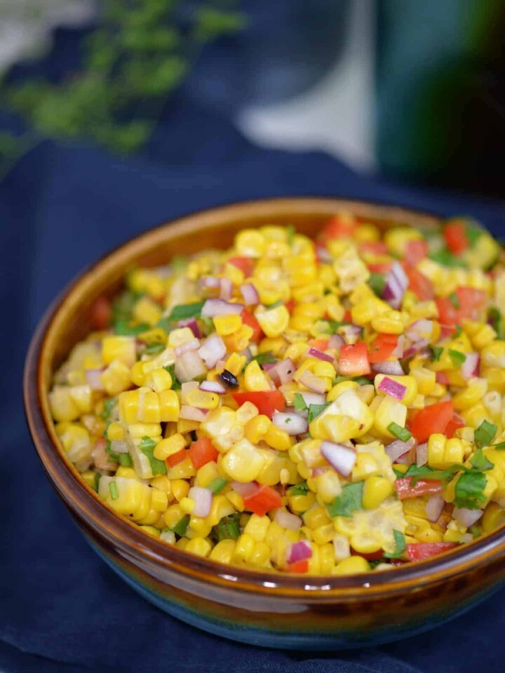 easy corn salsa recipe in a bowl, on top of a blue napkin | foodology geek.