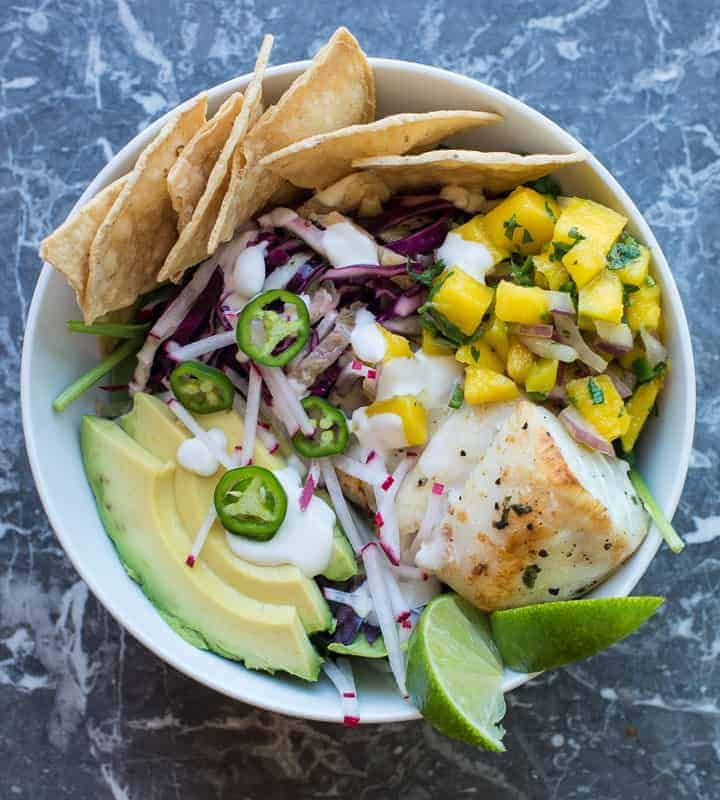 healthy fish taco bowl with mango salsa and mexican slaw in a white bowl