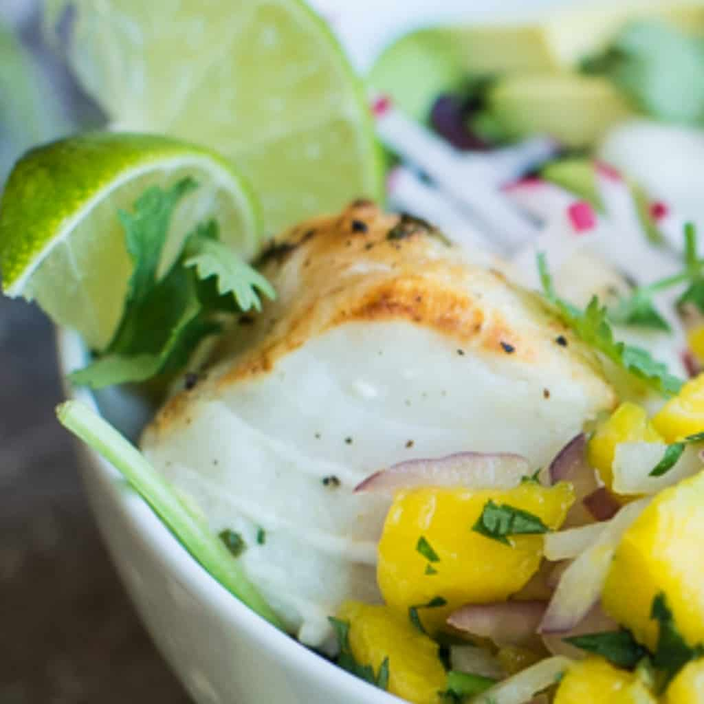 tequila lime marinated cod in a bowl with mango salsa and fresh limes