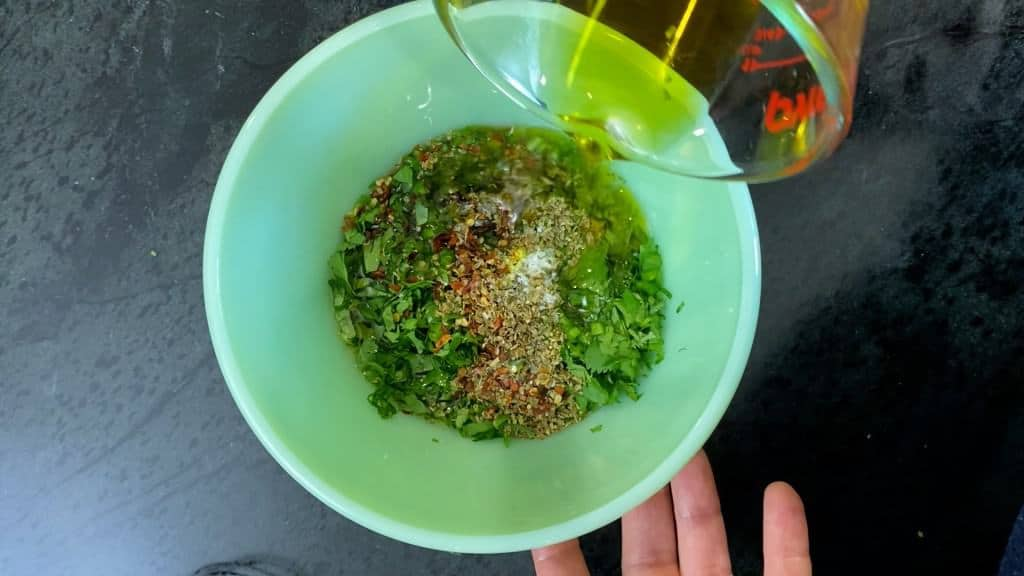 adding the olive oil to chimichurri