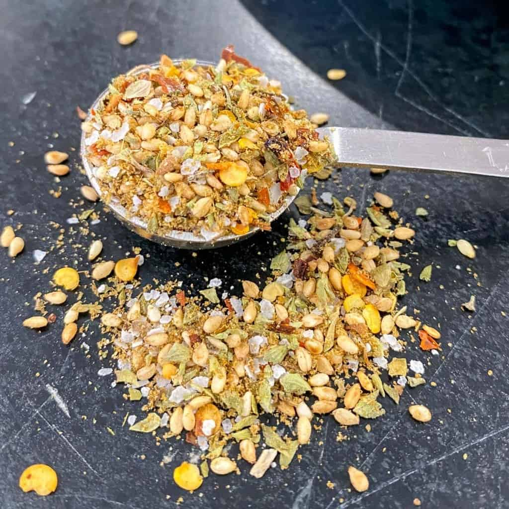mediterranean seasoning blend recipe in a teaspoon on a black counter top