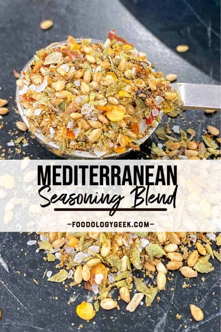 mediterranean seasoning blend pictured on a black counter top with a teaspoon full of herbs and spices