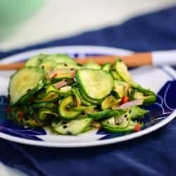 asian cucumber salad recipe in a blue and white bowl with chopsticks