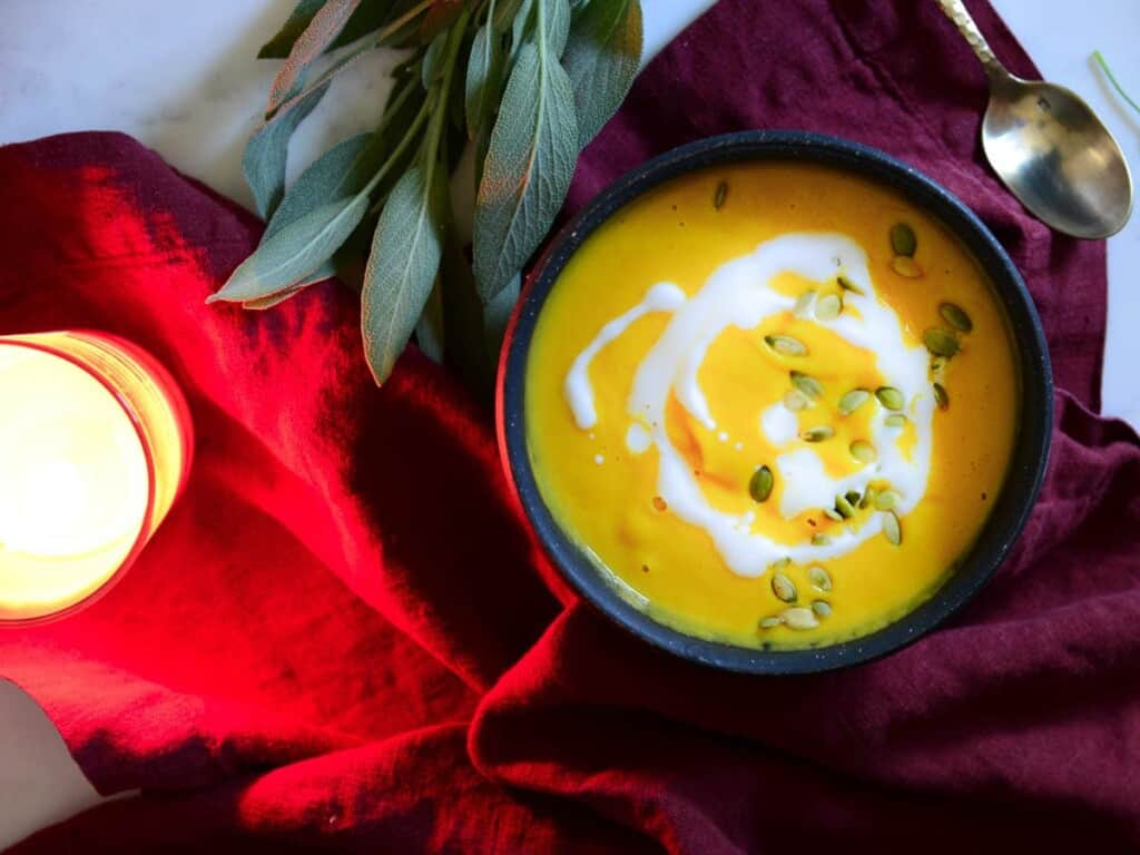 butternut squash soup with sage on a table with a red napkin and candles