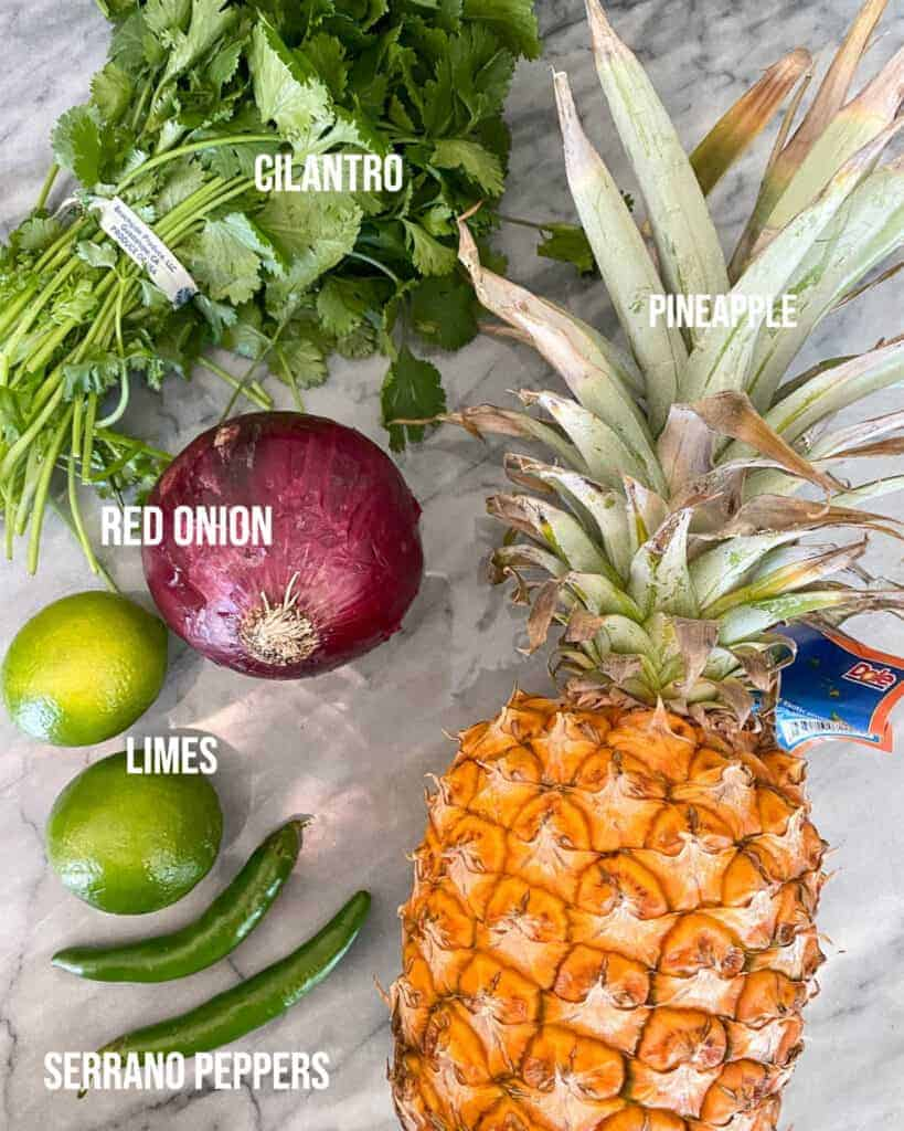 Ingredients used to make pineapple salsa on a marble board
