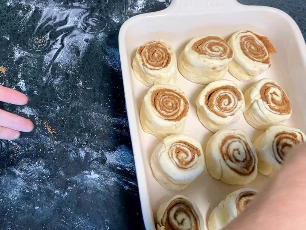 place the cut cinnamon rolls into a buttered 9x13 inch pan