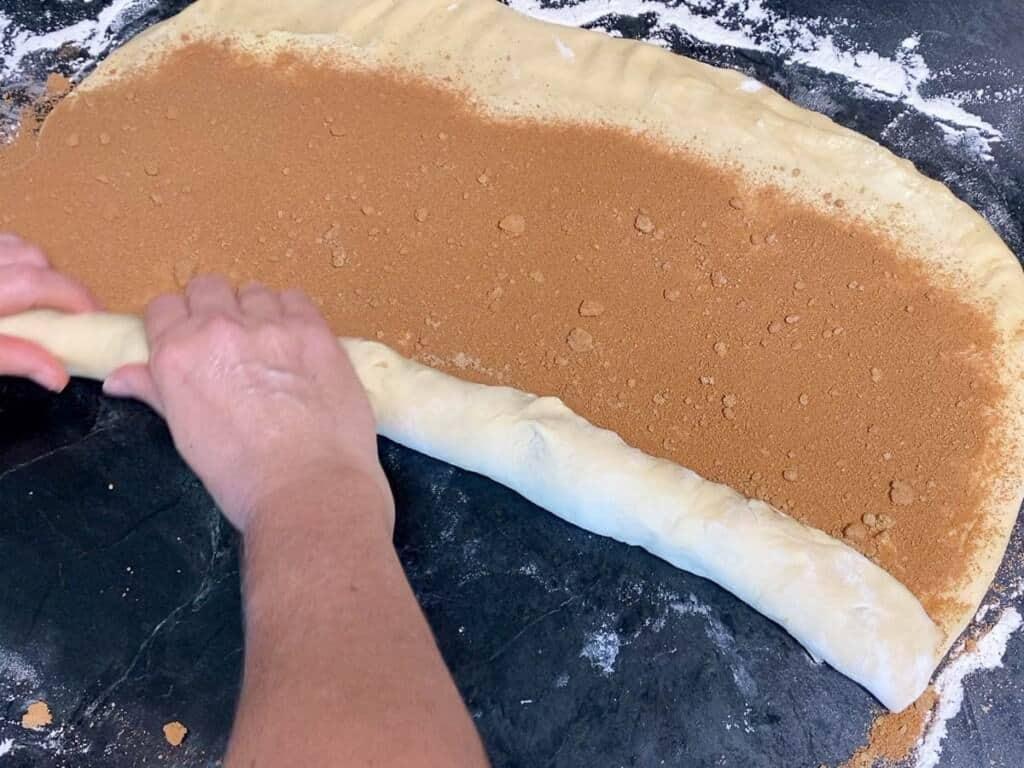 roll the cinnamon roll dough along the long side.