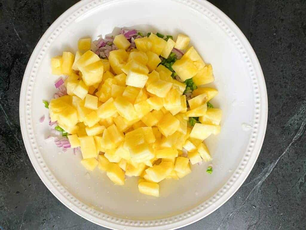 Step 2 of pineapple salsa. Dice the pineapple and add it to the bowl.
