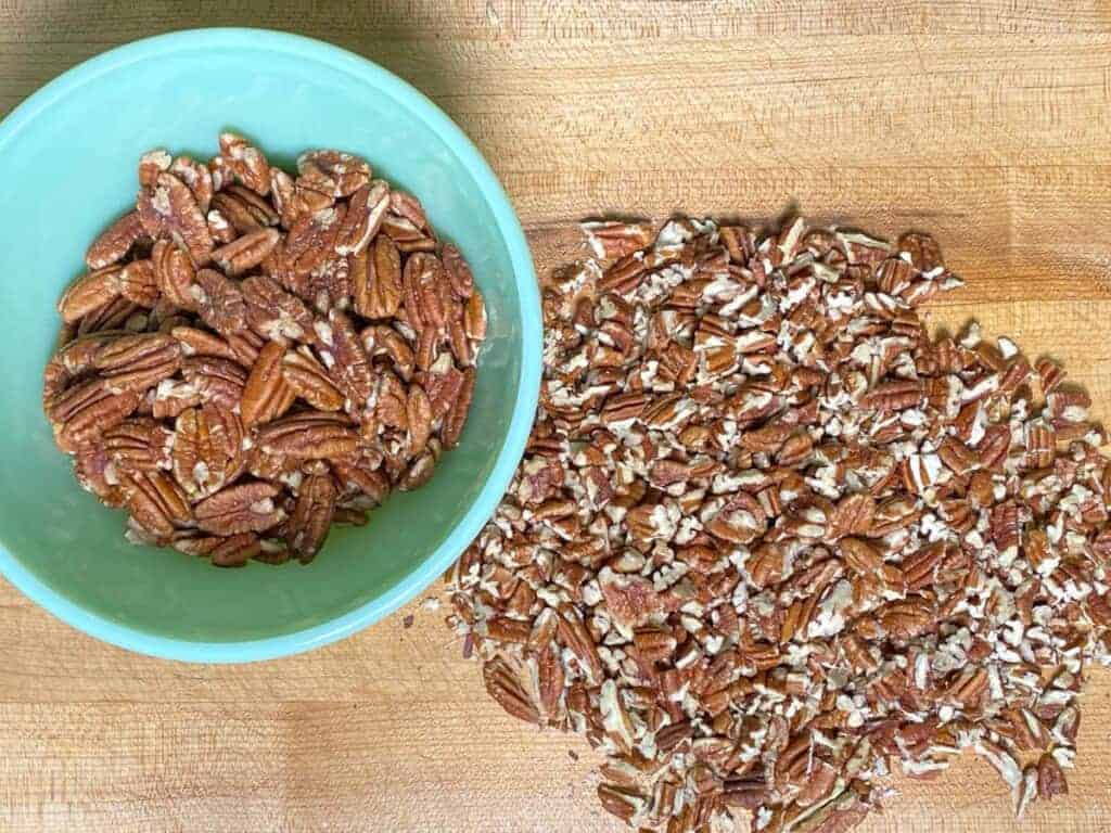 chopped pecan halves on a cutting board