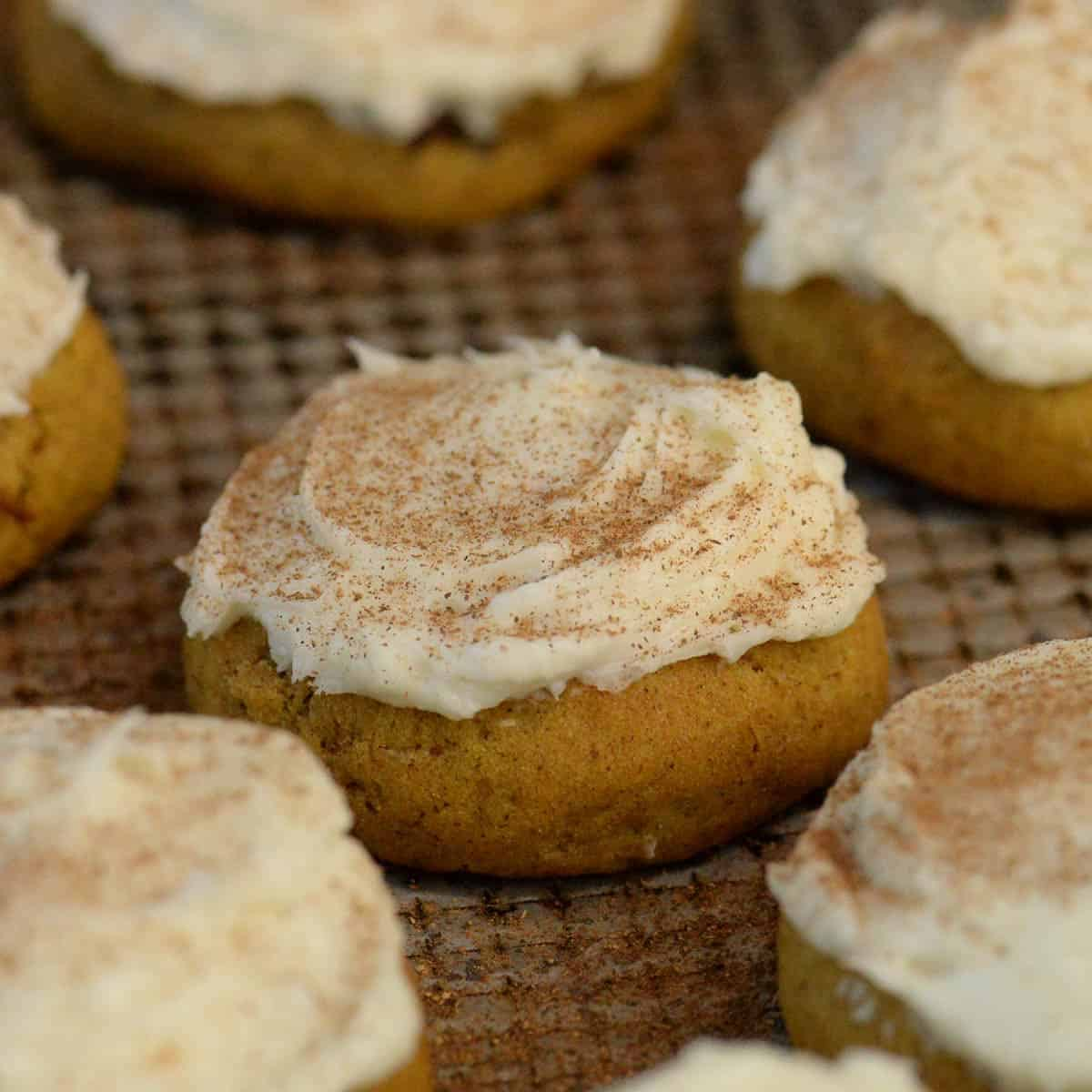 pumpkin cookies with cream cheese frosting on a metal baking sheet