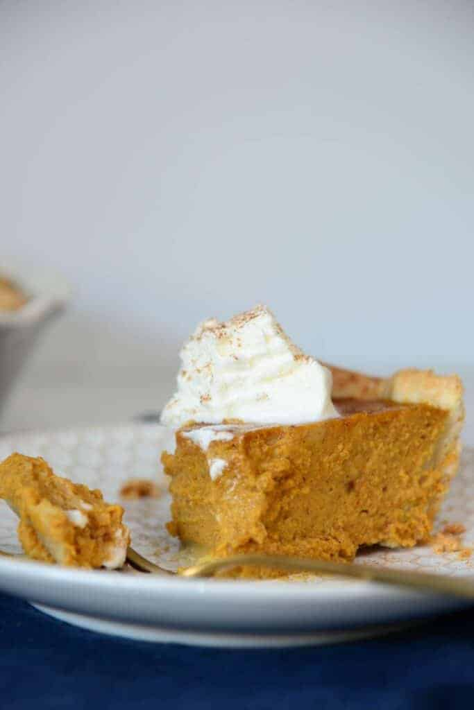 slice of pumpkin pie topped with whipped cream, one bite eaten out.