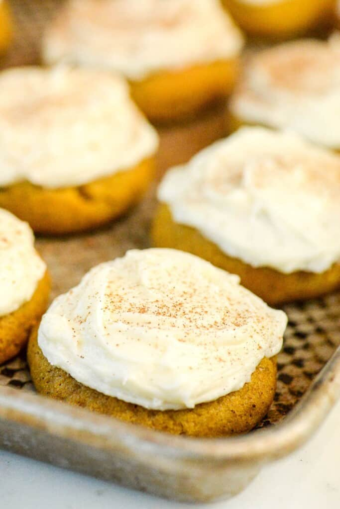 pumpkin cookies with cream cheese frosting on a baking sheet