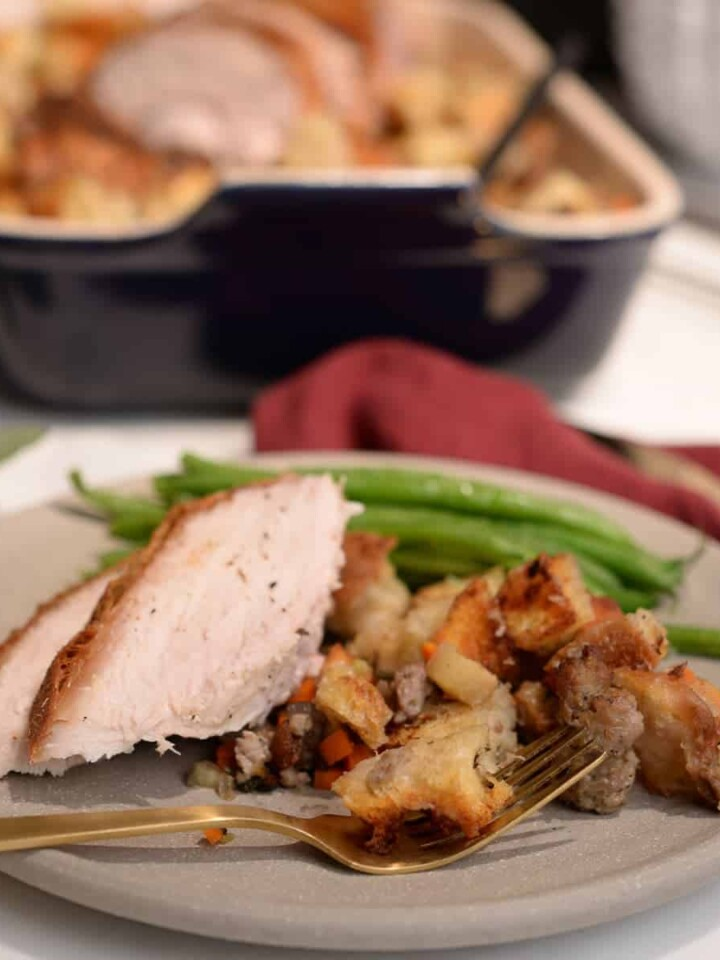 two slices of turkey with stuffing and green beans