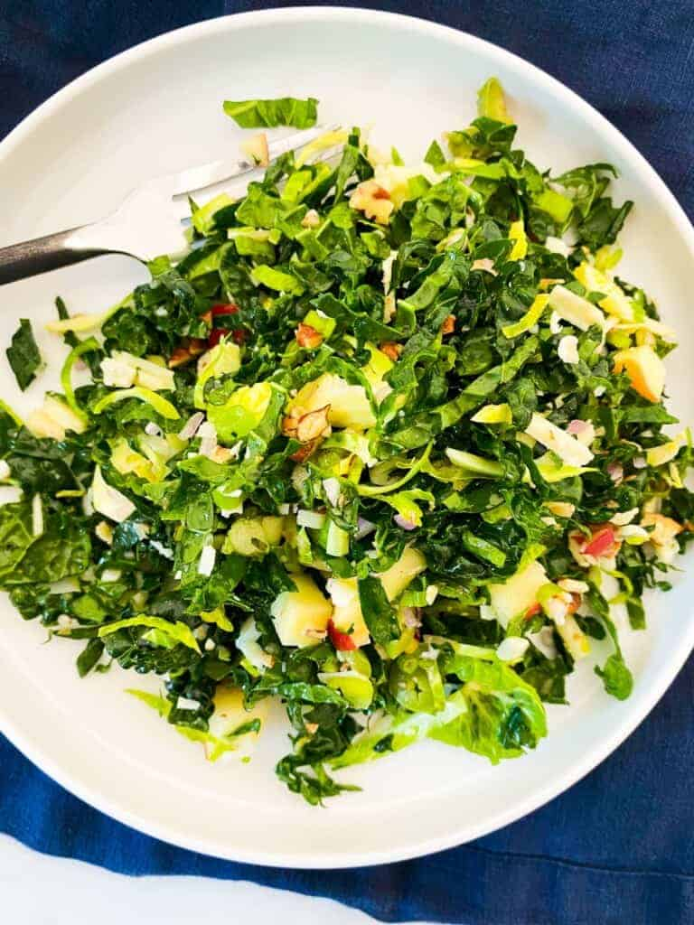 the best fall salad recipe on white plate with a navy blue napkin