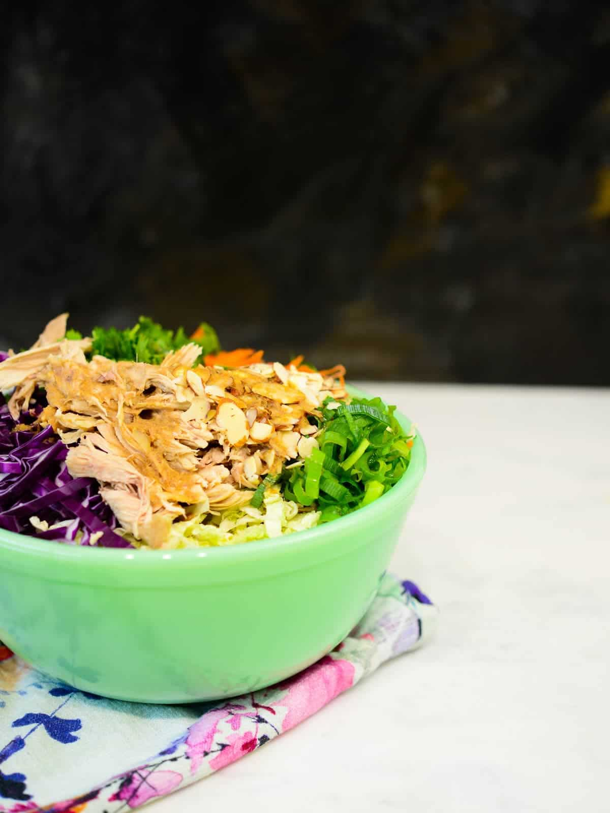 asian chicken salad in a green bowl
