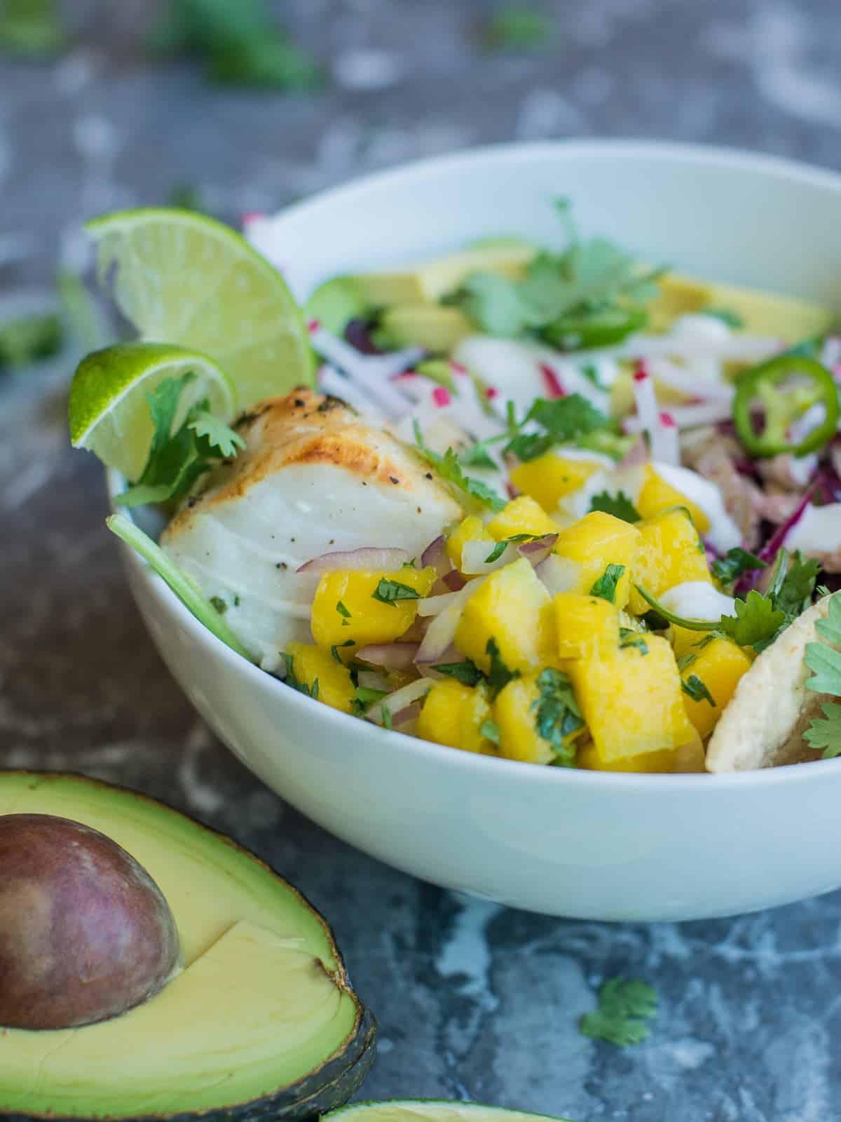 healthy fish taco bowl, fresh mango slasa on top