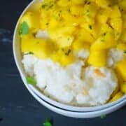 mango coconut rice in a bowl. coconut sticky rice topped with fresh mangoes.