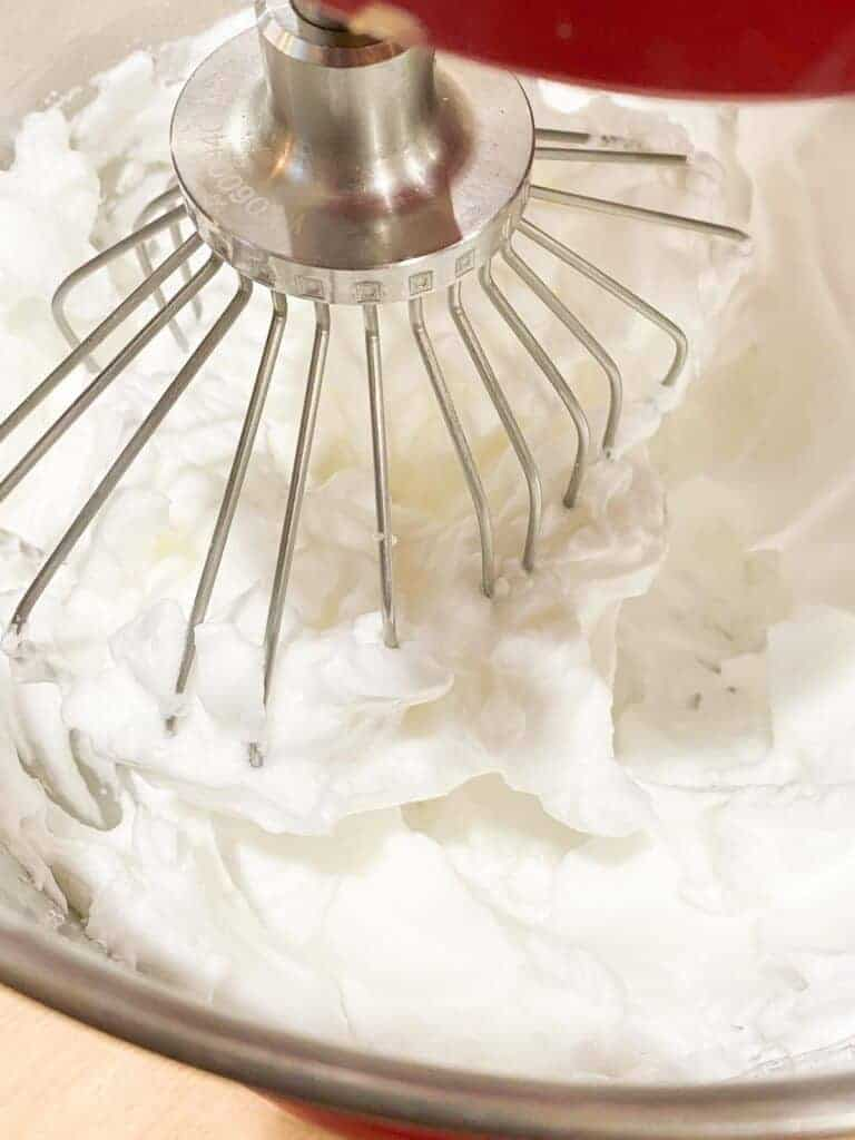 Keto marshmallows being whipped in a stand mixture fitted with a whisk attachment.
