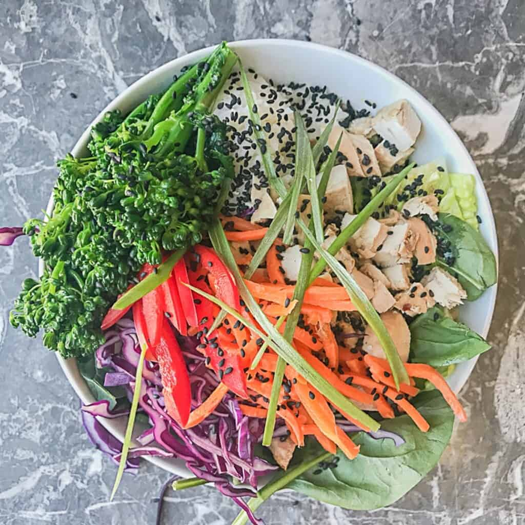 lettuce and spinach with sesame ginger dressing and a scoop of sushi rice and teriyaki chicken, red cabbage, carrots, red peppers, broccoli, green onions, and sesame seeds
