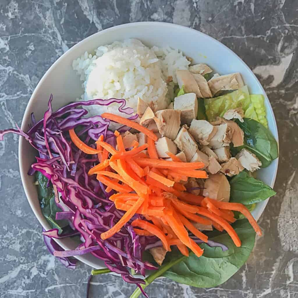 lettuce and spinach with sesame ginger dressing and a scoop of sushi rice and teriyaki chicken, red cabbage, and carrots