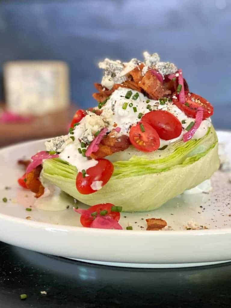 the perfect wedge salad. Cool, crisp iceberg lettuce topped with homemade blue cheese dressing, crispy bacon, fresh tomatoes and chives.