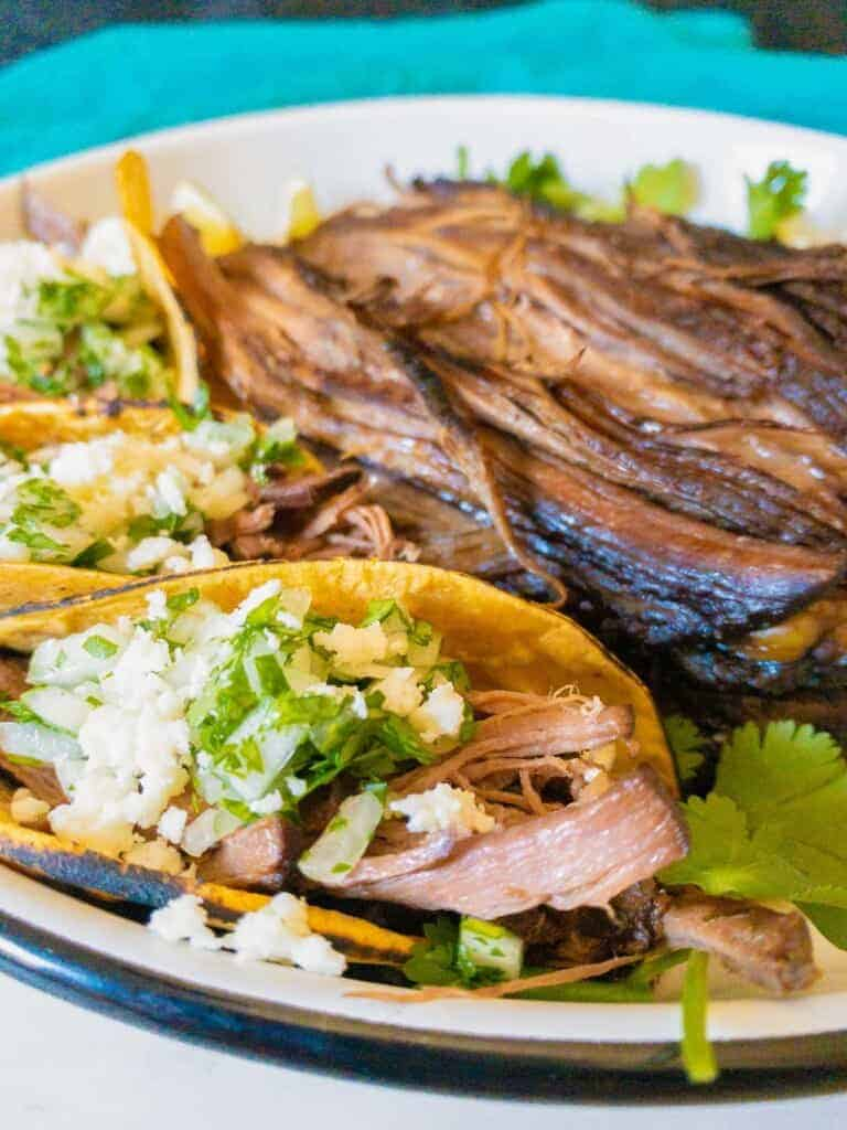 shredded beef tacos with cotija cheese and cilanto and onions