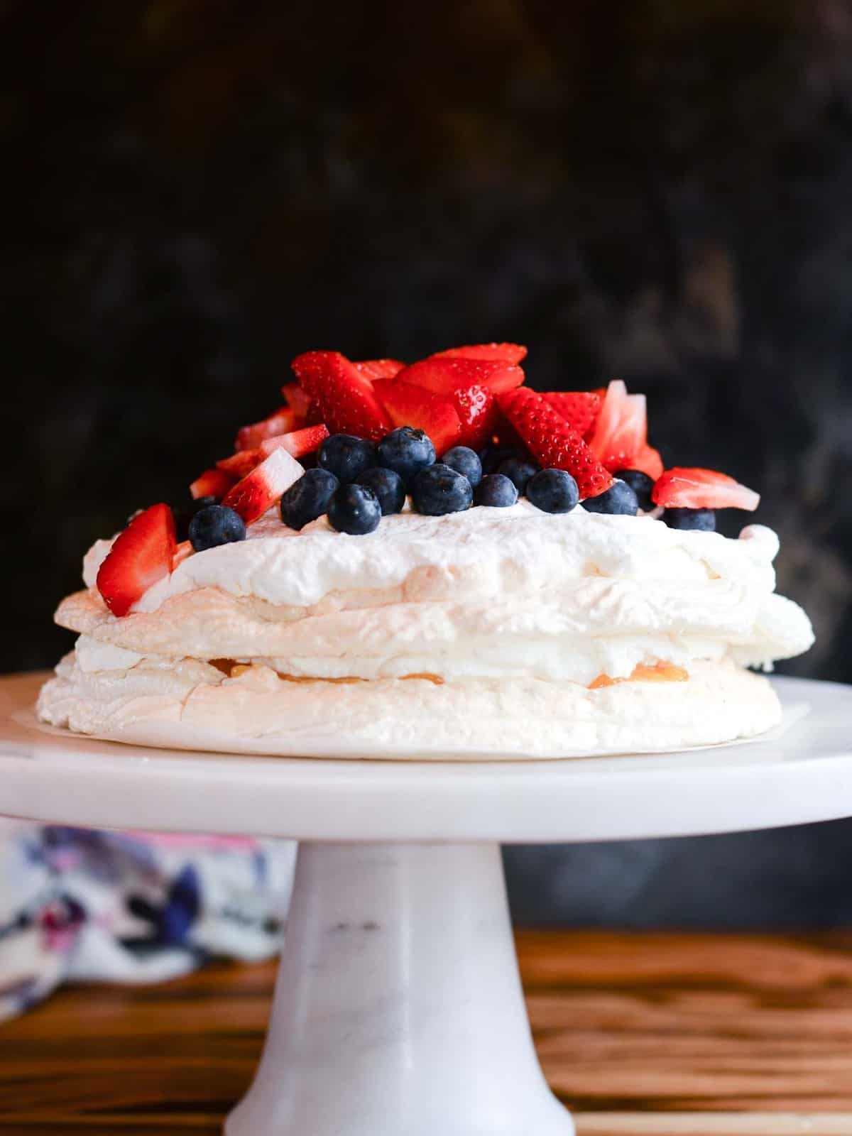 pavlova cake with lemon curd and fresh whipped cream presented on a marble cake stand