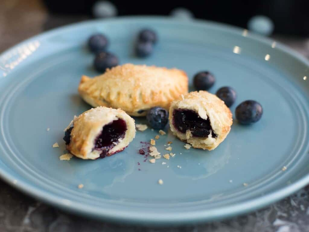 two blueberry hand pies with flaky crust and homemade blueberry pie filling on a blu plate