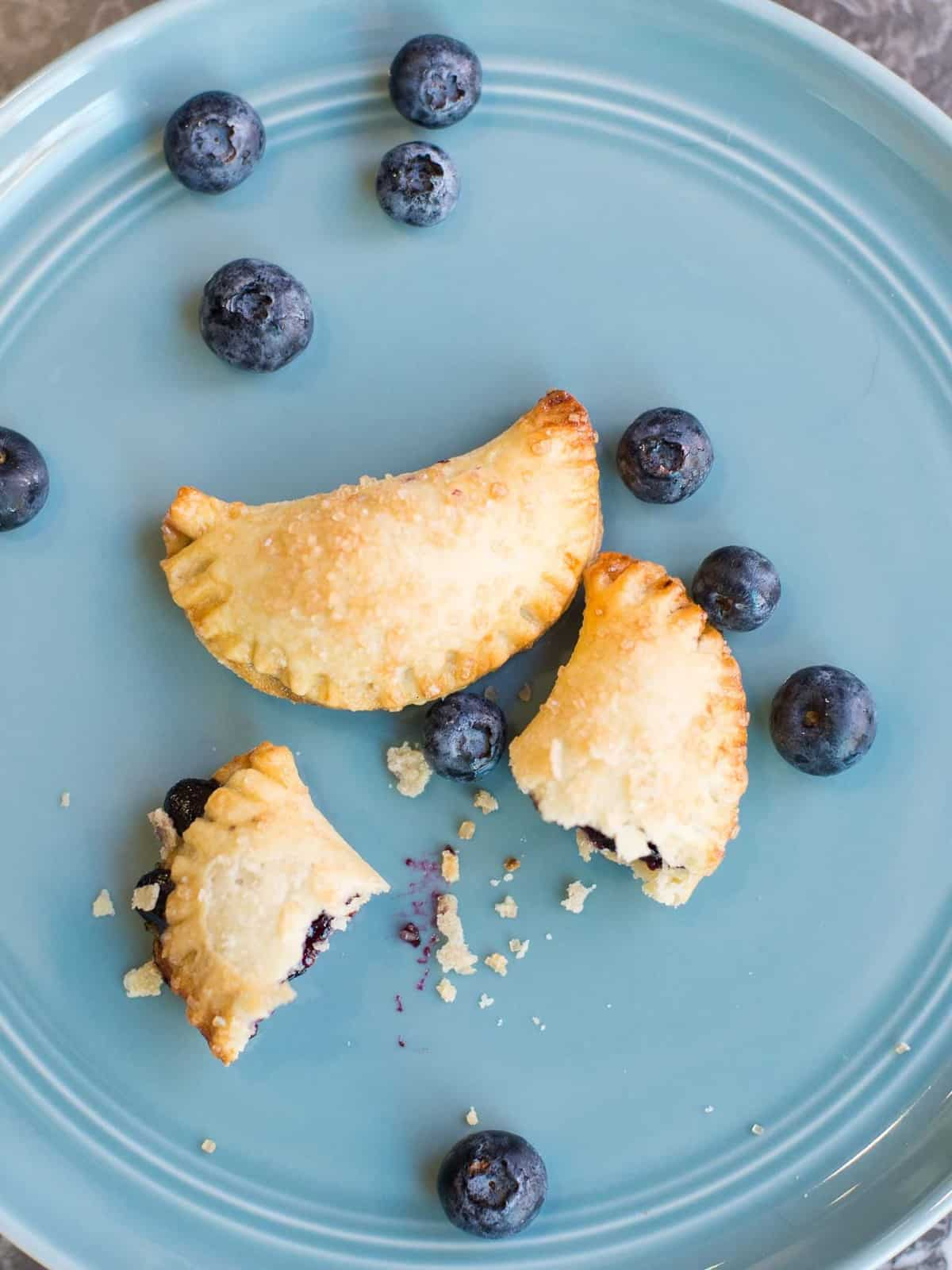 two blueberry hand pies on a plate with fresh blueberries. One is broken ope to show the blueberry pie filling.